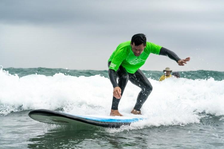 Un participante con impedimento visual siente el gusto de correr una ola durante la clínica. Foto: ISA / Sean Evans