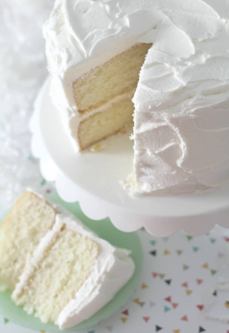 Favorite Vanilla Bean Cake on white cake stand with slice of cake on small green plate
