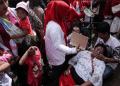 Seorang ibu pingsan akibat berdesak-desakan ketika berebut sembako gratis dalam gelaran Pesta Rakyat 'Untukmu Indonesia', di Monas, Sabtu (28/4). Foto: CNN Indonesia