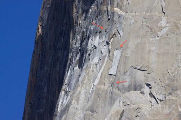 The climber on the right in yellow has lowered himself on a rope while the climbers on the left continue their ascent