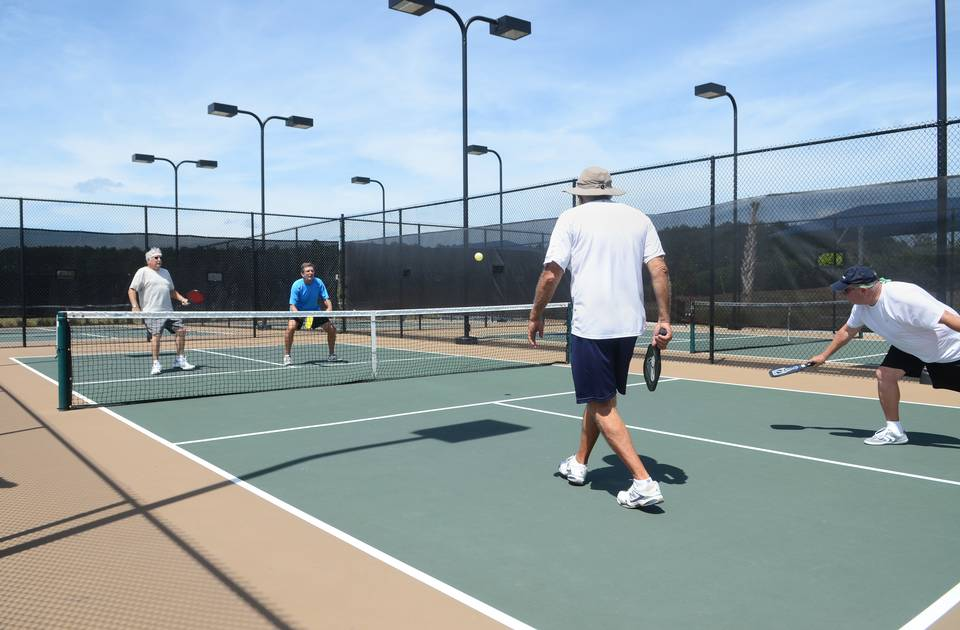 Pickleball is played by four players and, at 20 by 44 feet, a pickleball court resembles a miniature tennis court.