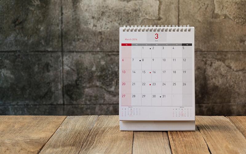 A Calendar On A Wood Table