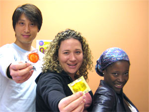 Three people handing out condoms to prevent infections
