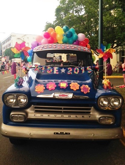 Vintage truck with rainbow balloon arch and streamers