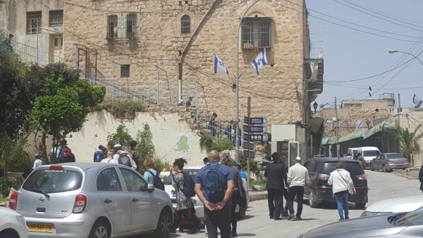 Israelis and colonial settlers celebrate outside the kindergarten on Shuhada street, while Palestinian children are made to pass through a military checkpoint every day on their way to school.