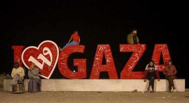 People sit by a colourful installation on Gaza's Al-Rasheed street Photo: (MEE/Mohamed al-Hajjar)