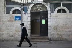 Jew walks next to synagogue