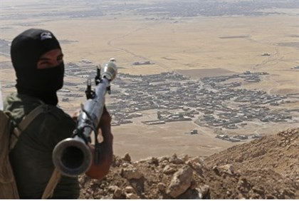 A Kurdish fighter hold a position overlooking IS-controlled territory in Iraq