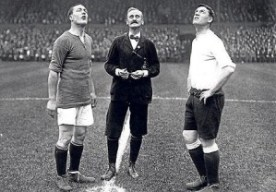 The captains of Chelsea and Spurs wait for the referee's coin to land, September 6, 1913