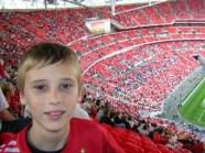 Un copil pe fundalul imensei tribune a stadionului Wembley