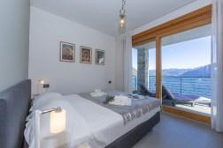 Slaapkamer 1 met 2-persoonsbed en uitzicht op het Comomeer