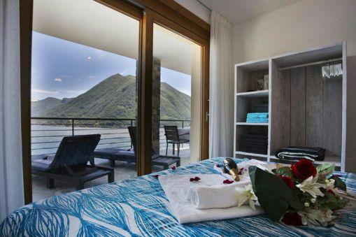 Slaapkamer 1 met 2-persoonsbed en toegang tot het terras met uitzicht op het Comomeer