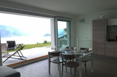 Woonkamer met schuifdeuren naar het terras en de tuin met uitzicht op het Comomeer