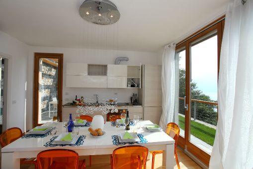 Woonkamer met uitzicht op het Comomeer en volledig uitgeruste open keuken