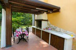 Groet prive-tuin met overdekt terras en buitenkeuken