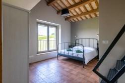 Slaapkamer met 2-persoonsbed en trap naar de vide
