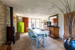 Eetkamer met lange tafel en openslaande deuren naar de tuin en het zwembad