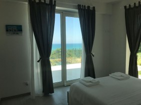Slaapkamer met 2-persoonsbed en uitzicht op zee
