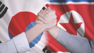 Closeup of two business partners shaking hands after deal business with flag of South Korea and North Korea in the background