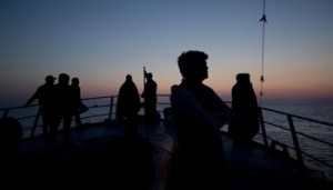 In this April 7, 2017, migrants aboard of Golfo Azurro look towards Sicily a day after being rescued by members of Proactiva Open Arms NGO. (ANSA/AP Photo/Bernat Armangue) [CopyrightNotice: Copyright 2017 The Associated Press. All rights reserved.]