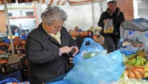 Una anziana paga la frutta acquistata in un mercato a Pisa in una foto d'archivio. ANSA / FRANCO SILVI
