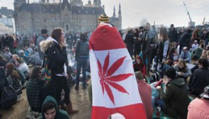 A man wears a Canadian maple leaf flag with marijuana leaf during the annual 4/20 rally on Parliament Hill in Ottawa, Ontario, Canada on April 20, 2018. (Photo by Lars Hagberg / AFP)        (Photo credit should read LARS HAGBERG/AFP/Getty Images)