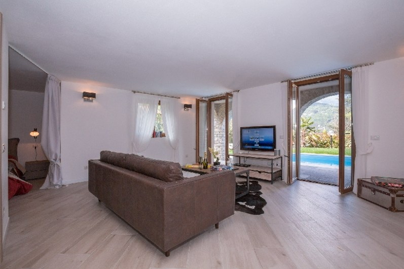 Second living room or bedroom with sofa bed to the ground floor with direct access to the garden and pool