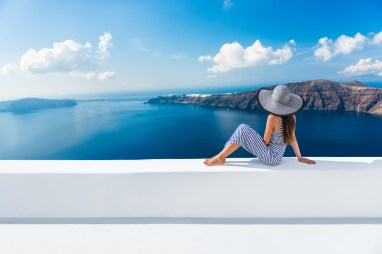 Europe Greece Santorini travel vacation. Woman looking at view on famous travel destination. Elegant young lady living fancy jetset lifestyle wearing dress on holidays. Amazing view of sea and Caldera