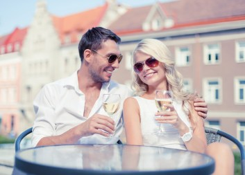 Smiling couple in sunglasses drinking wine in cafe in an european city