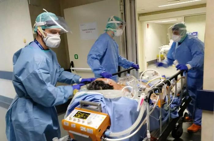 Sanitari italiani con un paziente affetto da Coronavirus Covid-19 nella terapia intensiva del Poliambulanza di Brescia (Ph. Ansa / Filippo Venezia).