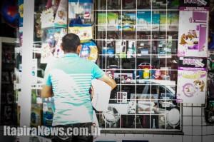 Consumidor observa vitrine em Itapira