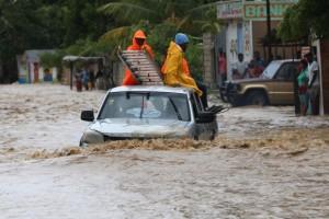 Um grupo de pessoas tenta cruzar uma via alagada in Leogane, no Haiti, após a passagem do Furacão Matthew (Orlando Barria/EPA/Agência Lusa)