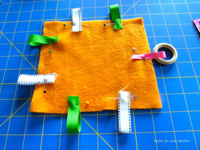 Ribbons pinned on taggie toy. http://www.itchinforsomestitchin.com