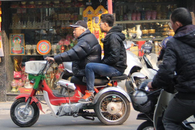 Man with no legs riding a motorcycle in Hanoi, Vietnam