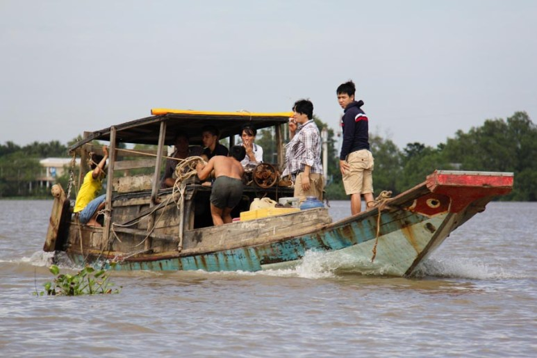 Workers heading out by boat in My Tho, Vietnam