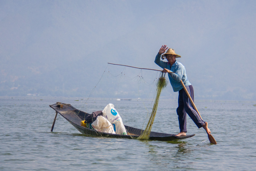 Fisherman posing while putting out a net on Inle Lake, Myanmar