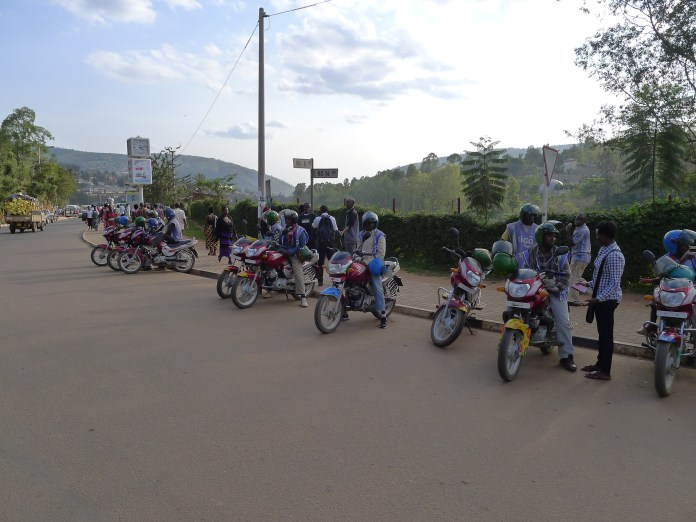Motorcycle taxi drivers wait for fares.