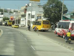 Conventional buses running next to TransCaribe busway