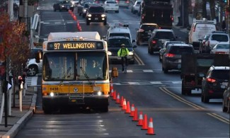 An MBTA bus travels along a temporary dedicated bus lane created by traffic cones in Everett, MA.