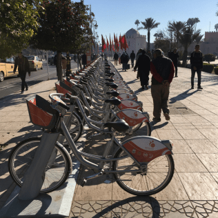 The city of Marrakech opened the first bike share system in Africa in 2016, launched in time for the city's hosting of the United Nations Climate Change Conference (COP22). While the system is relatively small—300 bikes in 10 stations—and only available in the city center, it has helped revive cycling in the city; people had traditionally traveled by bike before cars dominated the streetscape. Expanding the system, called Medina Bike, is one of several strategies being considered to reduce Morocco's fossil fuel consumption.