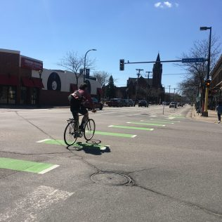 Man on bicycle without helmet crossing street at intersection in Whittier, neighborhood in Minneapolis, Minnesota, USA