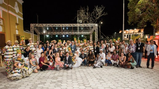 Large group of people smiling with traditional Brazilian dancers