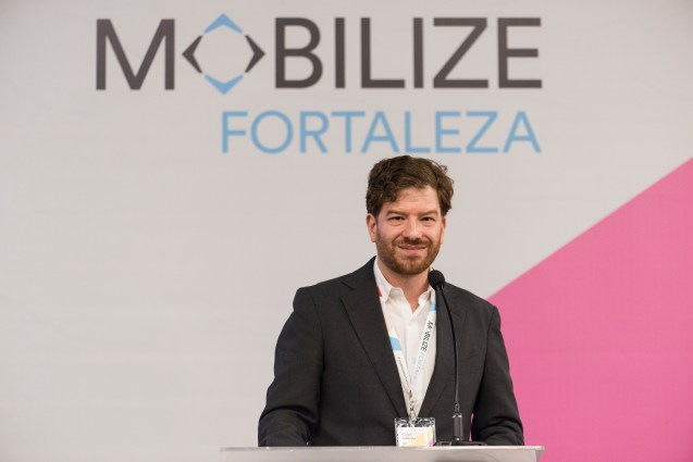 """Man in jacket and white shirt stands before wall emblazoned with """"MOBILIZE, Fortaleza"""""""