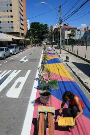 Woman painting a protected pedestrian area with bright pink, blue, and yellow