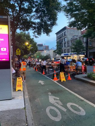In Manhattan's Upper West Side, a restaurant spilled out onto the street, with space for cyclists.