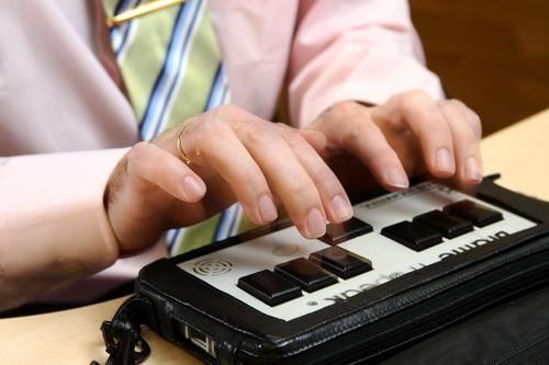 detalle de las manos de una persona utilizando el Braille´n Speak