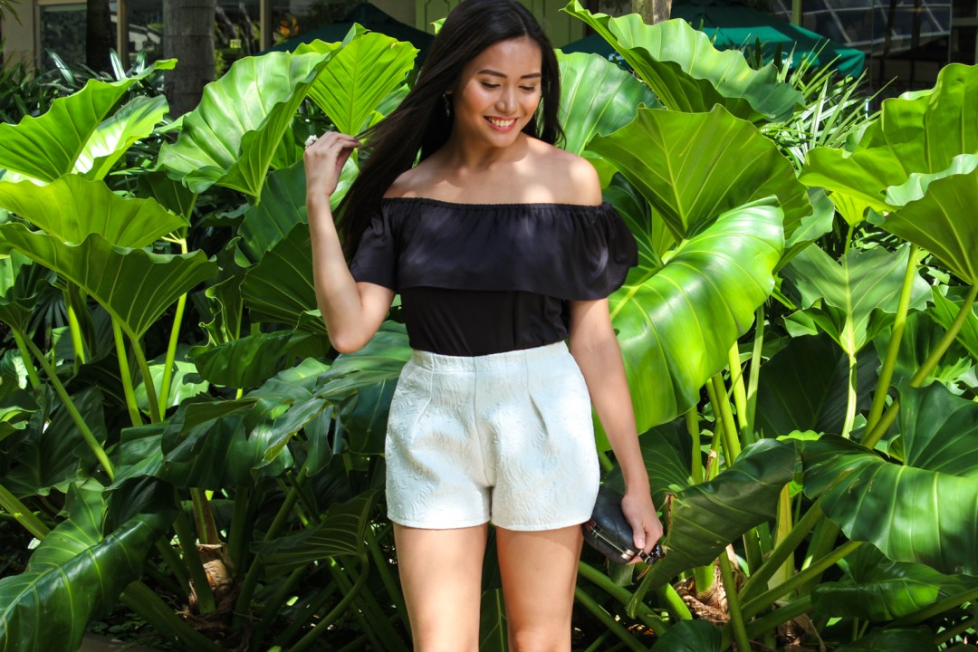 Adi Amor wearing a black off shoulder top with white shorts