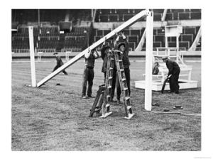 """Goal posts being installed at Wembley stadium before the 1936 Football Association Challenge Cup Final between Arsenal and Sheffield United. Wooden crossbars and uprights were used to make football goals in the days before extruded aluminum. In the background is the podium where a conductor in a white suit used to lead community signing before the footballers anthem"""" Abide with Me"""" as the finale before kick off."""