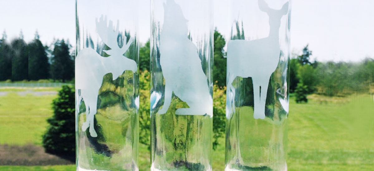 Glass bottles with animal drawings etching