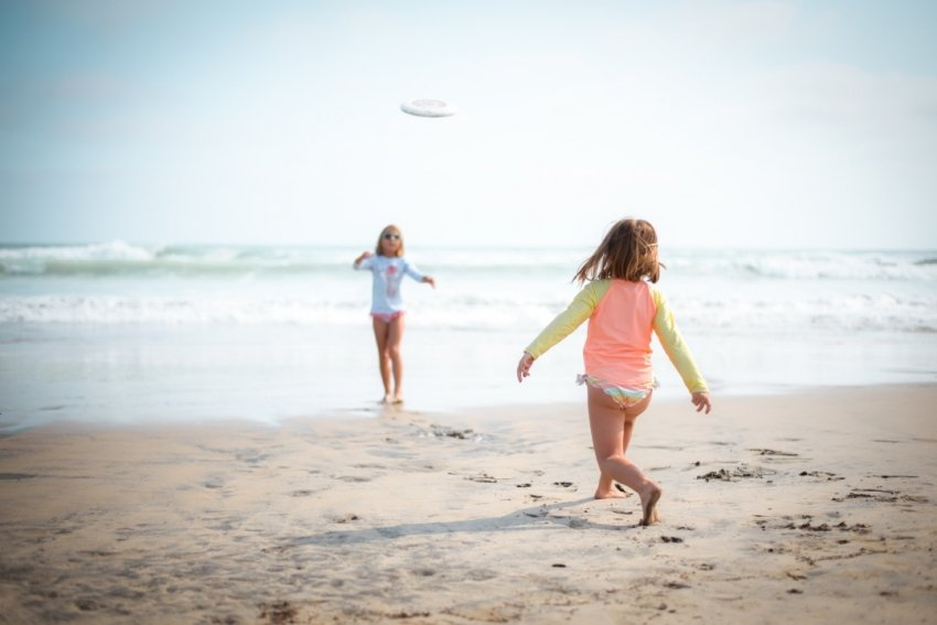 Girls playing frisbee on the beach